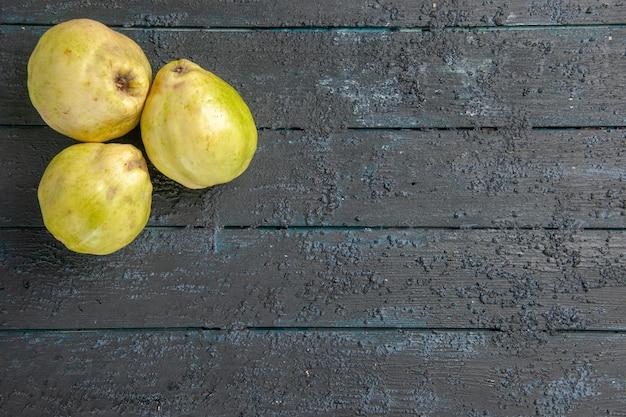 Top view fresh quinces mellow and sour fruits on dark-blue desk ripe plant fetus fresh tree sour fruit