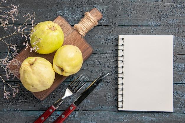 Vista dall'alto mele cotogne fresche frutti amari e morbidi su una pianta da scrivania scura albero da frutto fresco e acido maturo