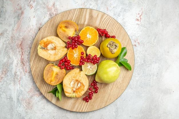 Вид сверху свежей айвы с другими фруктами на белом столе, свежих спелых фруктов