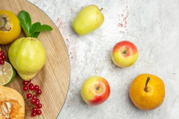 Вид сверху свежей айвы с другими фруктами на белом столе, спелые фрукты, спелые свежие