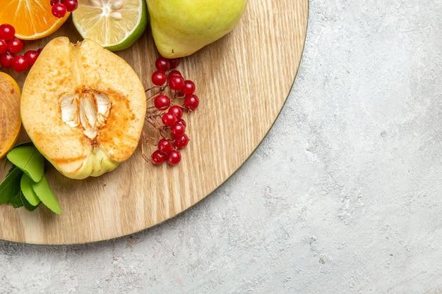 Vista dall'alto mele cotogne fresche con altri frutti sulla scrivania bianca frutta fresca matura dolce