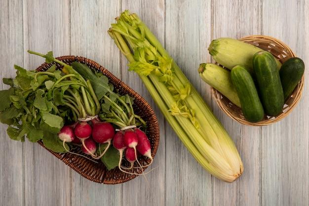 Vista dall'alto di ravanelli freschi su un secchio con cetrioli e zucchine su un secchio con sedano isolato su una grigia parete in legno