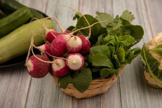 Top view of fresh radishes on a bucket with cucumbers and zucchinis on a plate with lettuce and cauliflower isolated on a grey wooden surface