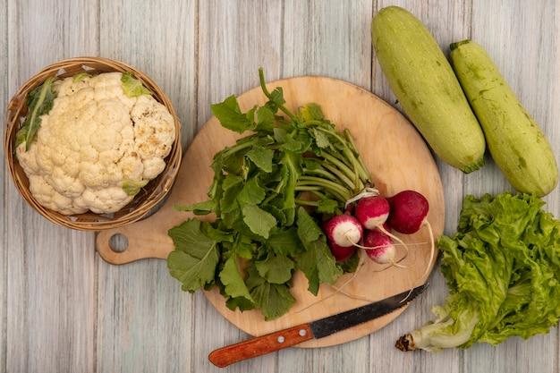 Vista dall'alto di ravanelli freschi su una tavola da cucina in legno con coltello con cavolfiore su un secchio con lattuga e zucchine isolato su una parete in legno grigio