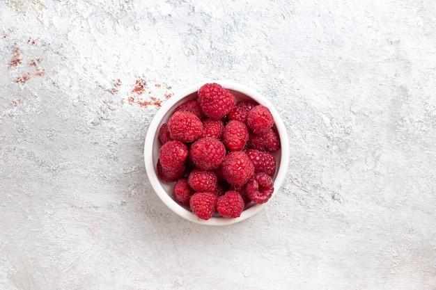 Вид сверху свежей малины внутри тарелки на белой поверхности ягодных фруктовых растений дикого дерева