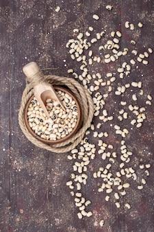 Vista dall'alto di fagioli freschi crudi all'interno della ciotola marrone e sparsi su tutto il fagiolo marrone, cibo crudo