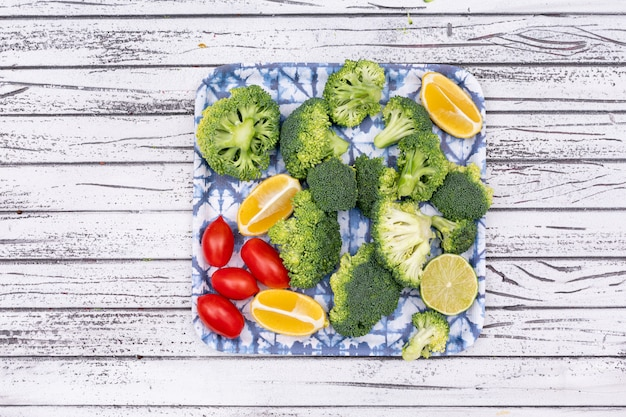 Top view fresh raw broccoli sliced lemon cherry tomatoes in plate on wooden surface