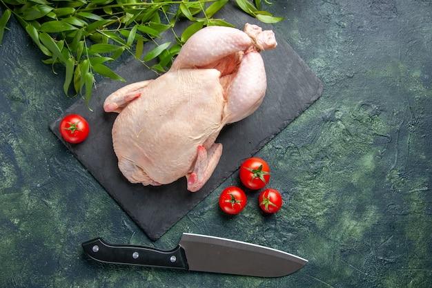 Vista dall'alto pollo crudo fresco con pomodori rossi su uno sfondo scuro pasto foto animale colore alimentare pollo carne da cucina