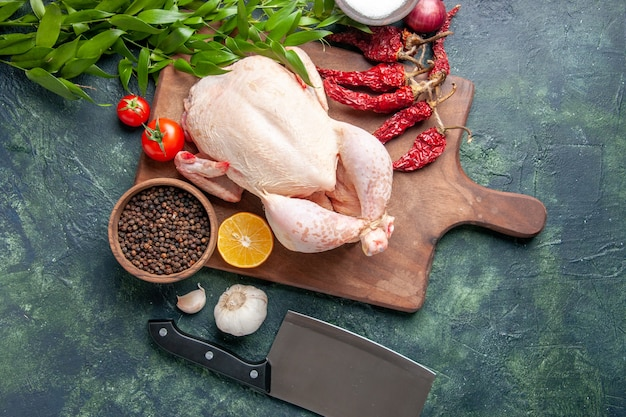 Vista dall'alto pollo crudo fresco con pomodori rossi su sfondo blu scuro cucina pasto foto animale cibo carne di pollo colore