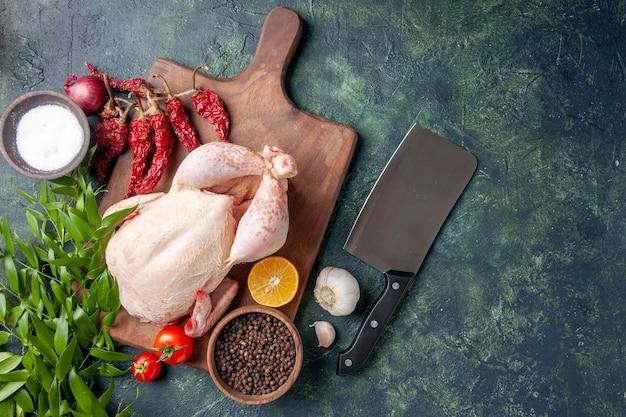 Vista dall'alto pollo crudo fresco con pomodori rossi su sfondo blu scuro cucina pasto foto animale cibo carne di pollo fattoria