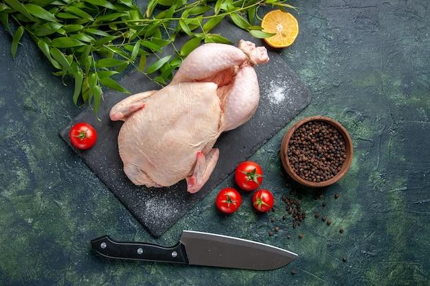 暗い背景の食事動物写真食品着色料チキンキッチンに赤いトマトと新鮮な生の鶏肉の上面図