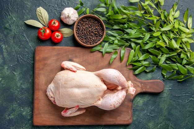 Vista dall'alto pollo crudo fresco con pomodori su sfondo blu scuro cucina ristorante pasto animale foto fattoria colore cibo carne di pollo