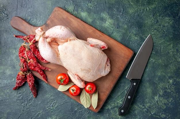 Vista dall'alto pollo crudo fresco con pomodori su sfondo blu scuro cucina ristorante pasto foto animale fattoria cibo carne di pollo colore