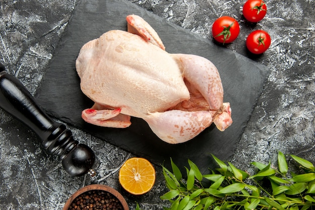 Top view fresh raw chicken with tomatoes on light-dark background kitchen meal animal photo chicken color farm food