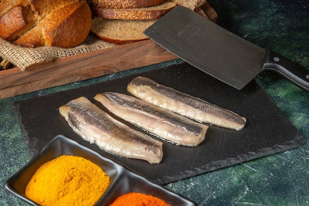 Vista dall'alto di pesce fresco crudo tritato sul tagliere di legno nero spezie pane mannaia