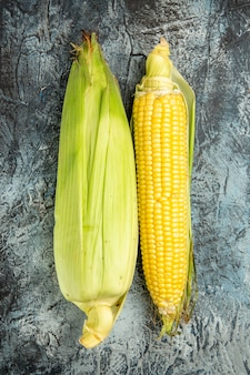 Pianta gialla del cereale crudo fresco di vista superiore sulla foto di colore verde scuro della tavola