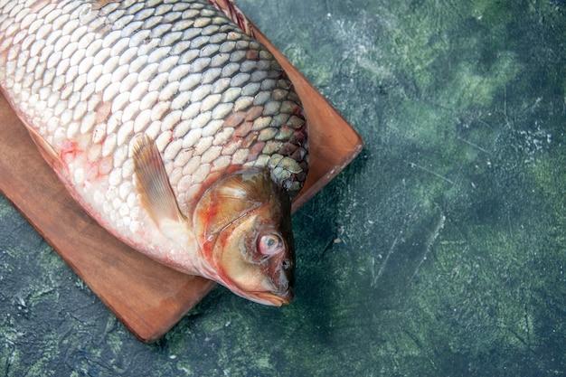 まな板の紺色の背景に新鮮な生の魚の上面図