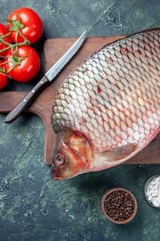 トマトの紺色の背景とまな板の上の新鮮な生の魚の上面図