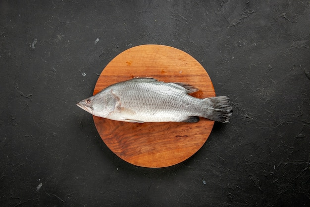 Top view fresh raw fish on round wood board on black table free space