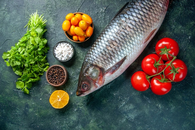Top view fresh raw fish with greens and tomatoes on dark background