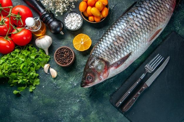 Vista dall'alto pesce crudo fresco con kumquat e verdure su sfondo scuro