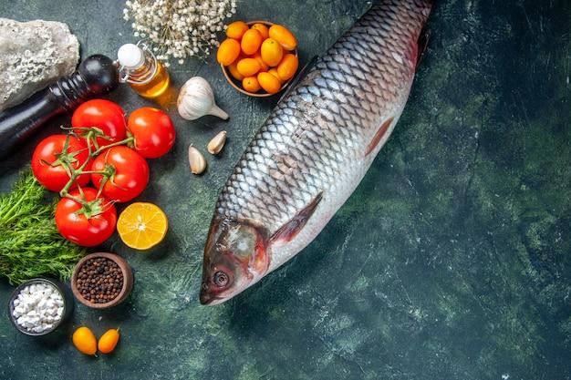 Top view fresh raw fish with kumquats and tomatoes on dark background