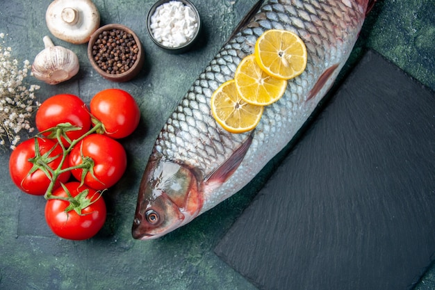Top view fresh raw fish with lemon slices and tomatoes on dark blue background
