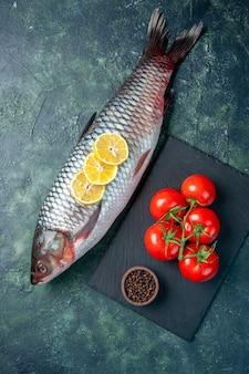 Vista dall'alto pesce crudo fresco con fette di limone e pomodori su sfondo blu scuro