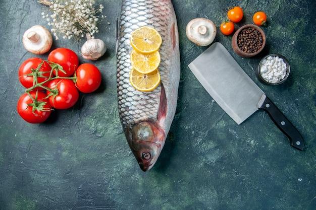 Vista dall'alto pesce crudo fresco con limone e pomodori su sfondo blu scuro