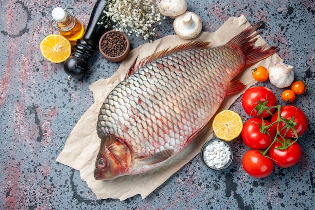 Top view fresh raw fish with red tomatoes on blue background