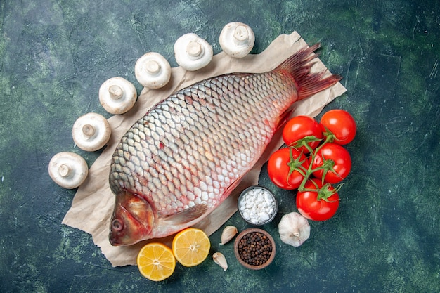 Vista dall'alto pesce crudo fresco con pomodori rossi e fette di limone su sfondo blu scuro