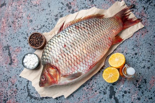 Vista dall'alto pesce crudo fresco con condimenti su sfondo blu