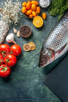 Вид сверху свежей сырой рыбы с помидорами и зеленью на темном фоне