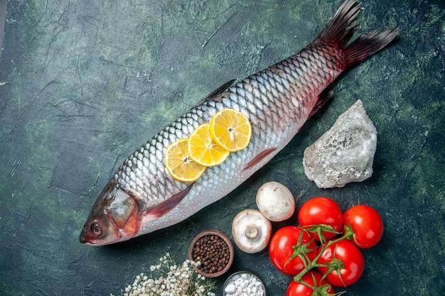 Вид сверху свежей сырой рыбы с помидорами и лимоном на темно-синем фоне