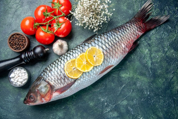 Top view fresh raw fish with tomatoes and lemon on dark blue background
