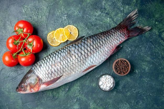 Vista dall'alto pesce crudo fresco con pomodori e fette di limone su sfondo blu scuro