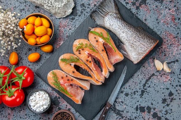 Vista dall'alto di verdure fresche di pesce crudo sul vassoio di colore scuro spezie pomodori con steli aglio fiori coltello kumquat su blu nero mescolare i colori tabella