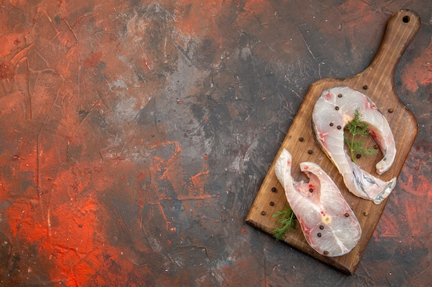 Top view of fresh raw fishes and pepper on wooden cutting board on mix color surface
