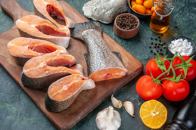 Top view of fresh raw fishes on wooden cutting board oil bottle fresh foods on dark mix colors table