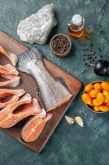 Top view of fresh raw fishes on wooden cutting board and oil bottle lemon kumquats garlic on dark mix colors table
