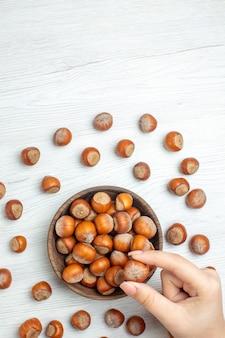 白い机の上の新鮮な生のヘーゼルナッツの上面図ナッツ映画植物食品クルミスナック