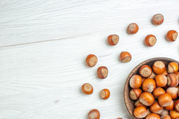 白い机の上に新鮮な生のヘーゼルナッツの上面図
