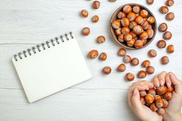 여성의 손에 있는 흰색 테이블에 있는 신선한 생 헤이즐넛