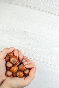 女性の手で白いテーブルに新鮮な生のヘーゼルナッツの上面図