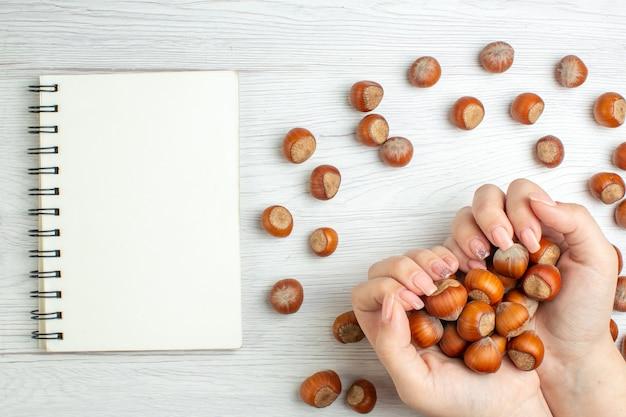 上面図白いテーブルナッツ植物食品スナック女性映画の新鮮な生ヘーゼルナッツ