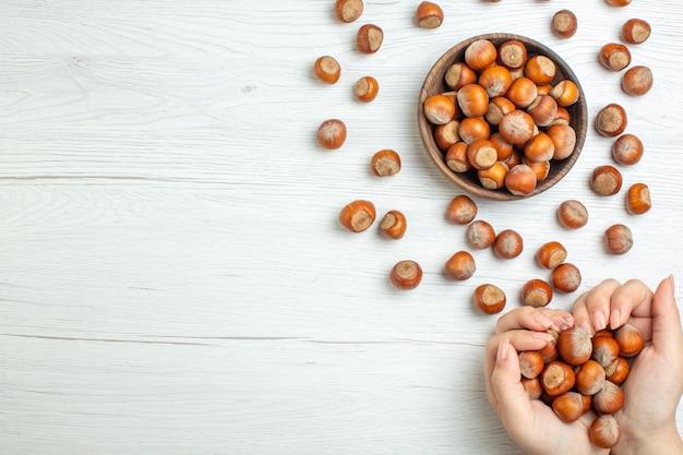 上面図白いテーブルに新鮮な生ヘーゼルナッツクルミナッツ植物食品スナック女性映画空きスペース