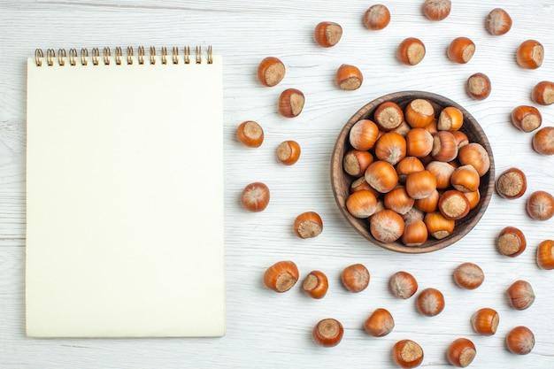 白い机の上にメモ帳とトップビューの新鮮な生ヘーゼルナッツ