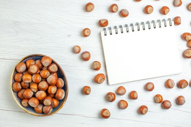 흰색 테이블에 메모장이 있는 신선한 생 헤이즐넛 호두 견과류 식물 식품 스낵 영화