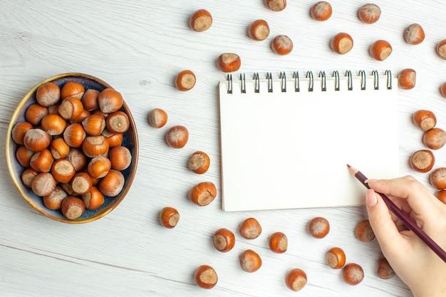 白いテーブルの上のメモ帳で新鮮な生のヘーゼルナッツの上面図