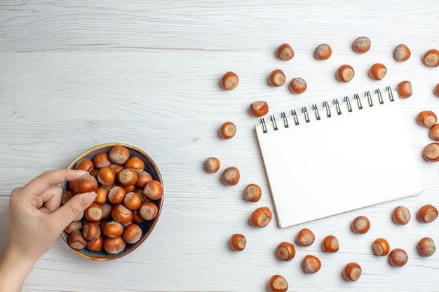 흰색 테이블에 메모장이 있는 상위 뷰 신선한 생 헤이즐넛